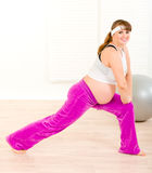 Smiling pregnant female doing stretching exercises Stock Photography