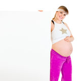 Smiling pregnant female holding blank billboard Stock Image