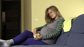 Smiling pregnant future mother play with newborn shoes stock footage