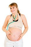 Smiling pregnant holding stethoscope on her belly Stock Image