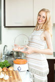 Smiling  pregnant housewife cooking potatoes with electric steam Stock Photo
