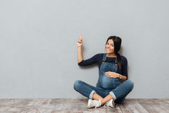 Smiling pregnant lady sitting on floor pointing to copyspace. Picture of smiling pregnant lady sitting on floor over grey background pointing to copyspace Stock Photo