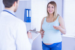 Smiling pregnant patient talking to doctor which is taking notes. In medical office Royalty Free Stock Photography