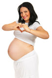 Smiling pregnant showing heart shape Royalty Free Stock Image