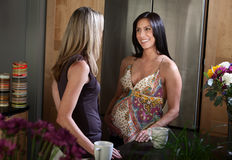 Smiling Pregnant Woman. Beautiful Hispanic pregnant woman with her friend in the kitchen Stock Image