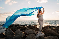 Smiling Pregnant Woman on the Beach with Blue Veil. A beautiful, smiling pregnant woman on a rocky beach at sunrise. She is holding a blue silk veil that's Royalty Free Stock Image