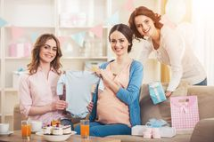 Pregnant Woman with Blue Baby Romper and Friends. royalty free stock images