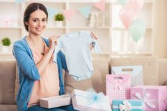 Smiling Pregnant Woman with Blue Baby Romper. royalty free stock photo