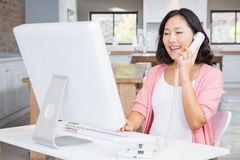 Smiling pregnant woman in a call on land line. At home Stock Photos