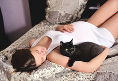 Smiling pregnant woman with cat at home. stock images