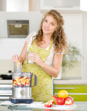 Smiling pregnant woman cooking in her kitchen. Royalty Free Stock Images