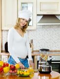 smiling pregnant woman cooking in her kitchen Stock Image
