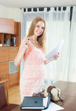 Smiling pregnant woman with documents in home interior Stock Image