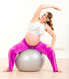 Smiling pregnant woman doing exercises on ball Stock Image