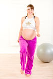 Smiling pregnant woman doing fitness exercises. Smiling beautiful pregnant woman doing fitness exercises at living room Stock Photography