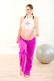 Smiling pregnant woman doing fitness exercises. Smiling beautiful pregnant woman doing fitness exercises at living room Royalty Free Stock Photo