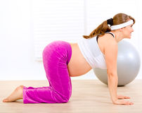 Smiling pregnant woman doing fitness exercises. Smiling beautiful pregnant woman doing fitness exercises at living room Stock Image