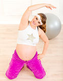 Smiling pregnant woman doing fitness exercises. Smiling beautiful pregnant woman doing fitness exercises at living room Royalty Free Stock Photography
