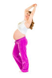 Smiling pregnant woman doing fitness exercises. Smiling beautiful pregnant woman doing fitness exercises isolated on white Royalty Free Stock Photography