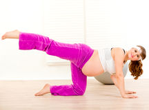 Smiling pregnant woman doing fitness exercises. Smiling charming pregnant woman doing fitness exercises at living room Royalty Free Stock Images