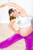 Smiling pregnant woman doing stretching exercises Stock Photography