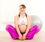 Smiling pregnant woman doing stretching exercises Stock Images