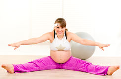 Smiling pregnant woman doing stretching exercises Stock Photo