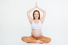 Smiling pregnant woman doing yoga exercise Royalty Free Stock Photo