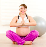 Smiling pregnant woman doing yoga exercises Stock Photos