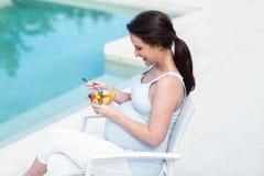Smiling pregnant woman eating fruit Stock Image