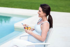 Smiling pregnant woman eating fruit Royalty Free Stock Photography