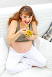 Smiling pregnant woman eating fruit salad Royalty Free Stock Photos