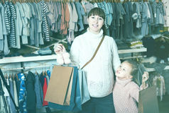 Smiling pregnant woman and girl boasting purchases Stock Photos