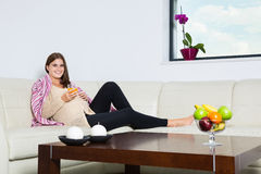 Smiling pregnant woman with a glass of orange juice. In couch Stock Photos