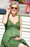 Smiling pregnant woman in green dress Stock Photography
