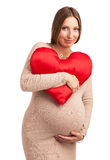 Smiling pregnant woman with heart shaped pillow Royalty Free Stock Image