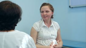 Smiling pregnant woman with her doctor in hospital room stock photo