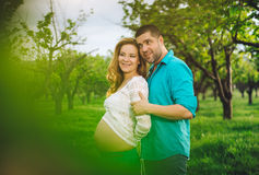Smiling pregnant woman and her husband in the wood at spring Stock Images