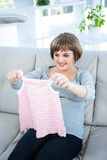 Smiling pregnant woman holding baby clothes Royalty Free Stock Photography