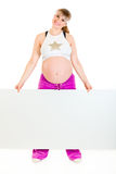 Smiling pregnant woman holding blank billboard Stock Photo