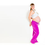 Smiling pregnant woman holding blank billboard Royalty Free Stock Photo