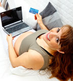 Smiling pregnant woman with laptop and credit card. Smiling beautiful pregnant woman on sofa at home with the laptop and a  credit card Stock Image