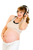 Smiling pregnant woman listening music in headphon Royalty Free Stock Photos