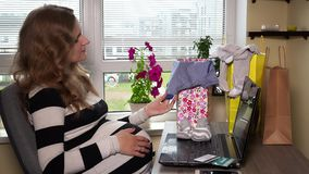Smiling pregnant woman looking at baby clothes after shopping online stock video