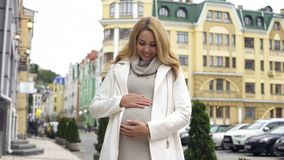 Smiling pregnant woman looking at her belly tenderly stroking it, maternity stock photography
