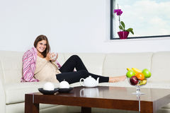 Smiling pregnant woman with mug of hot chocolate. In couch Royalty Free Stock Image
