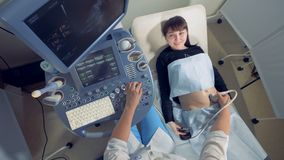 Smiling pregnant woman is observing her own ultrasound process. 4K stock footage