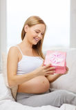 Smiling pregnant woman opening gift box Royalty Free Stock Photos