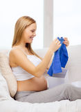 Smiling pregnant woman opening gift box Royalty Free Stock Images