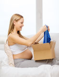 Smiling pregnant woman opening parcel box. Pregnancy, post, delivery and motherhood concept - smiling pregnant woman sitting on sofa and opening parcel box with Stock Image
